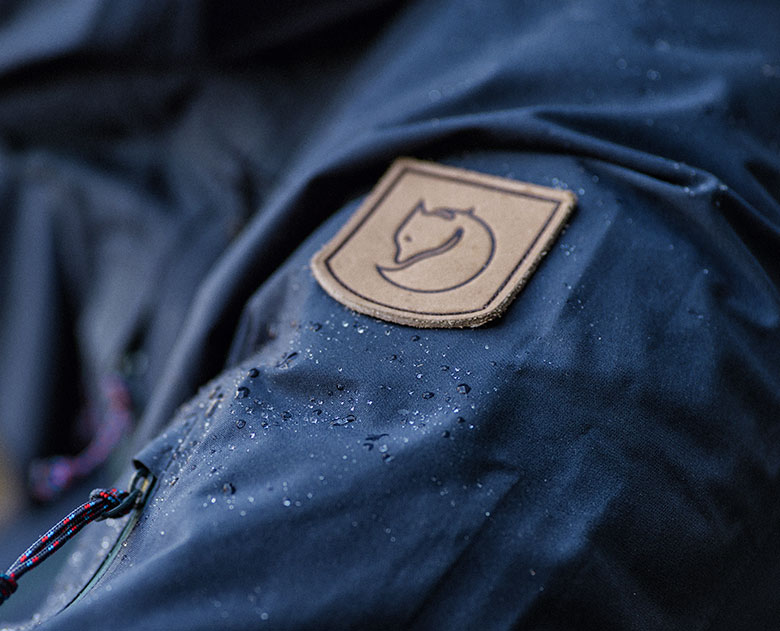 closeup picture of eco-shell jacket with fjallraven emblem