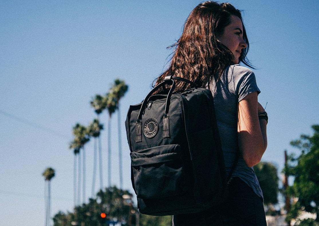 woman in a sunny environment wearing a Kanken black pack