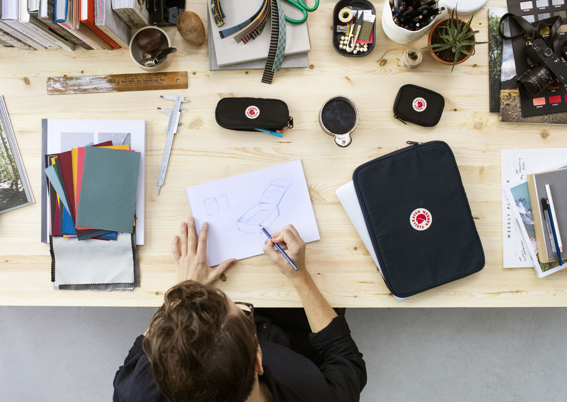 man sitting a workstation with fjallraven gear around him while he sketches