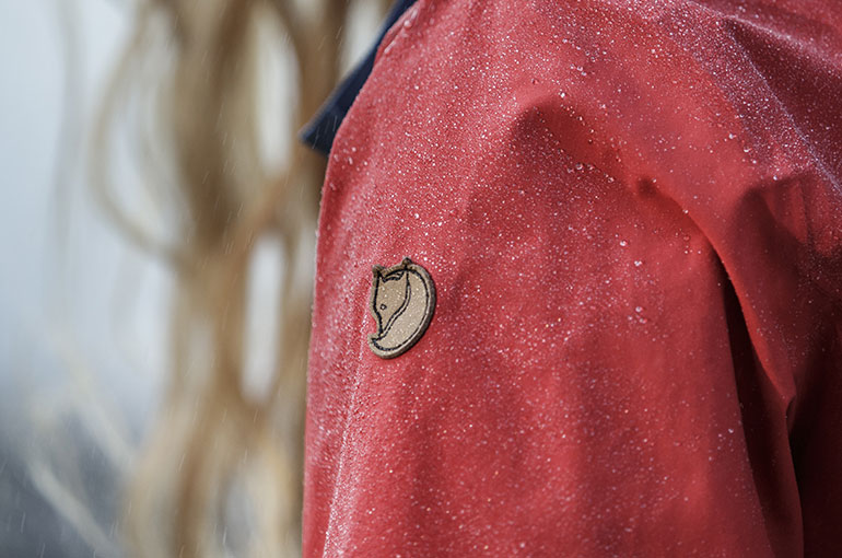 image of an the Fjallraven emblem on an eco-shell jacket with snow falling