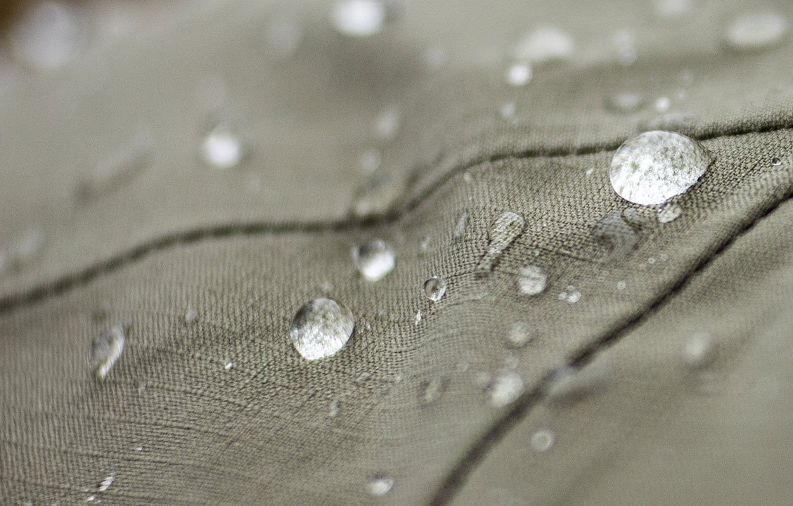 image of a piece of  eco-shell fabric with water beading on it